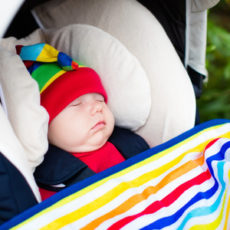 60323035 - cute little baby in funny colorful hat sleeping in infant car seat on a walk in a park